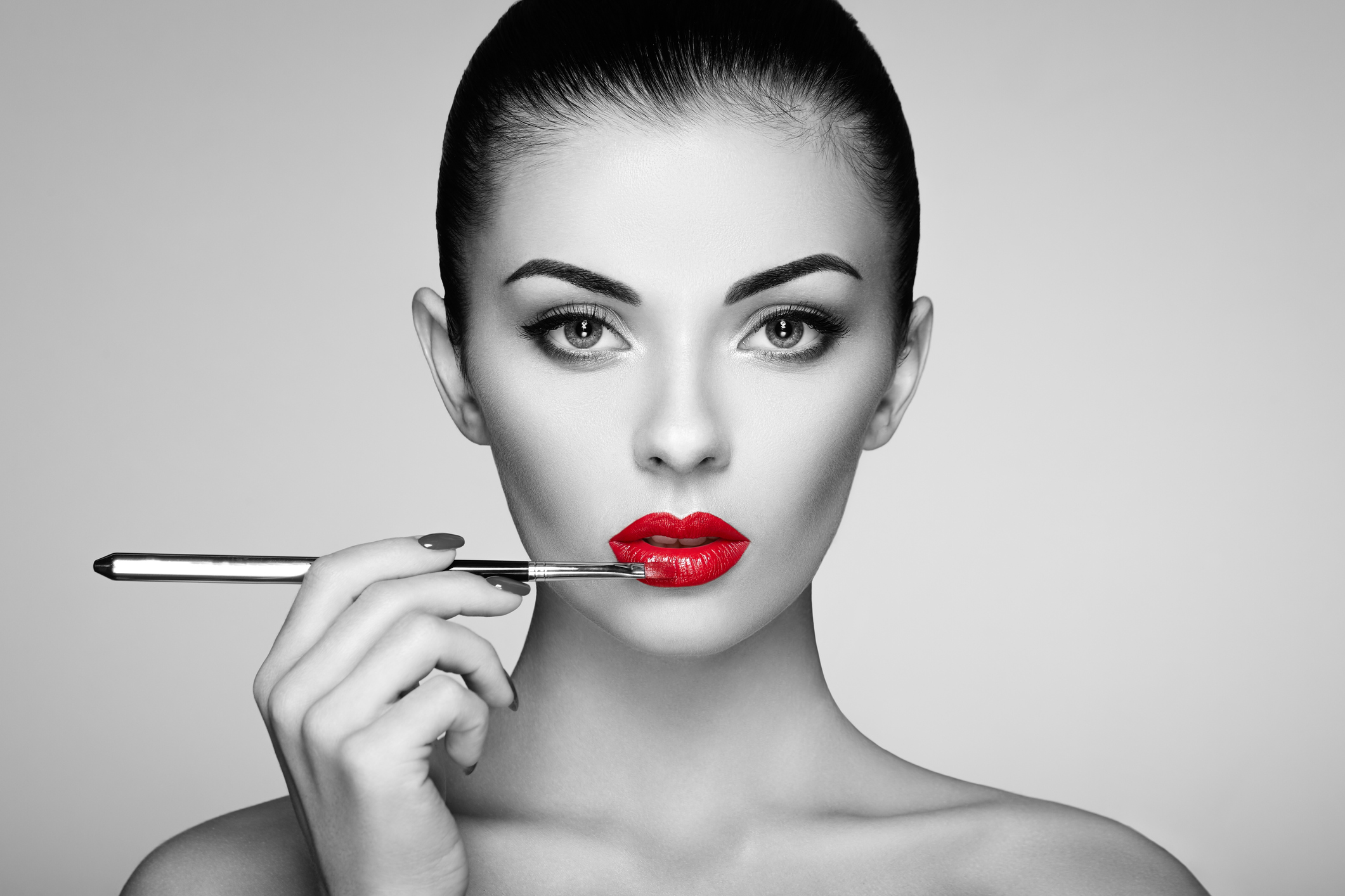 Black and white photo of woman painting lipstick. Beautiful woman face. Makeup detail. Beauty girl with perfect skin. Red lips and nails manicure
